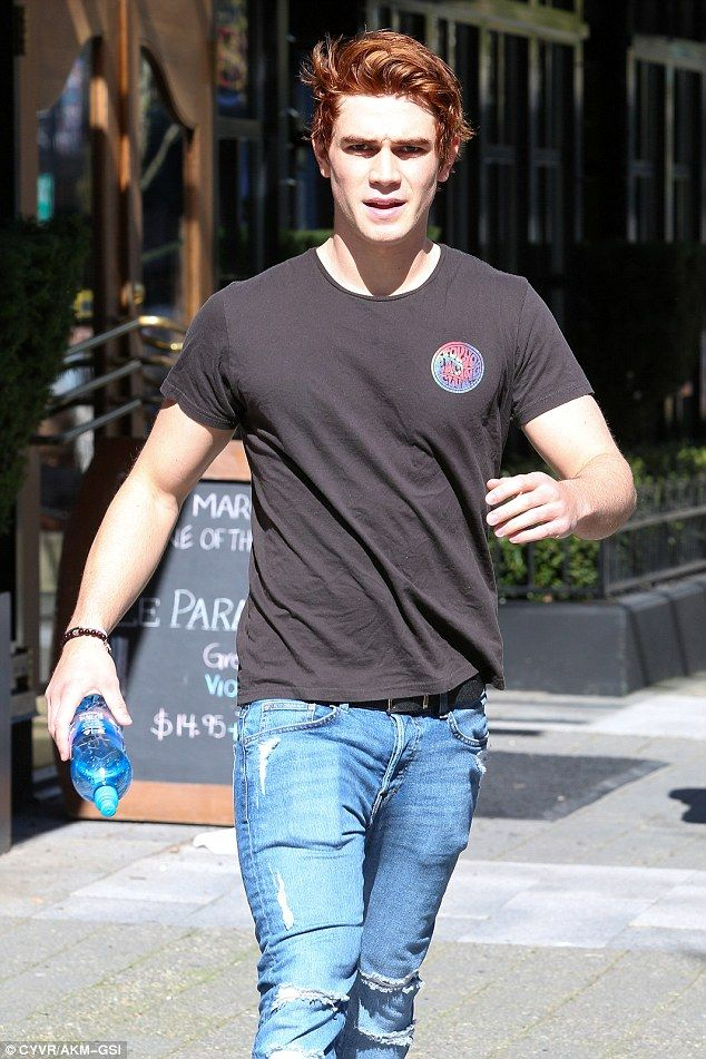 Casual:He opted to change into a black t-shirt with a hippy-style logo on the left side o...