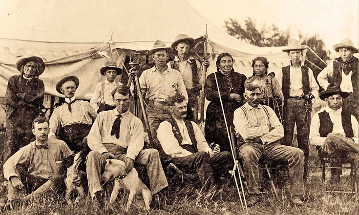 Holding a transit, rod and stakes, this allotment crew stood ready to divide land in Pine Ridge, in the newly formed South Dakota, circa 1890s. They were surrounded by, at far right, interpreter Billy Garnett (son of Fort Laramie Gen. Richard B. Garnett and Sioux mother Looks-At-Him), with wife Filla Janis, daughter and three sons. Also shown is John Brennan, wearing a stand up celluloid collar at far left, with son Paul behind him in the doorway; Brennan was probably working as South Dakota…