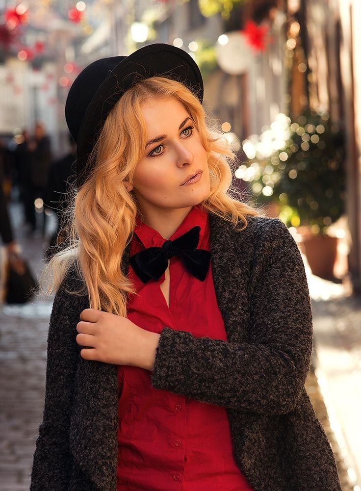 Christina Key trägt Fliege, eine rote Bluse und einen schwarzen Hut