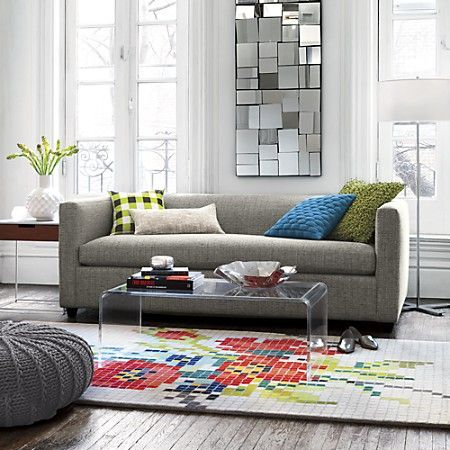Buy glass or clear items of furniture to create an illusion of a bigger space like this CB2 Peekaboo Clear Coffee Table