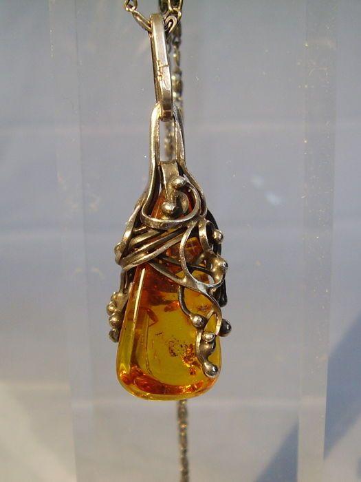Antieke handgemaakte amber hanger aan ketting Gdansk circa 1940  De hanger en de ketting zijn gemaakt van 925 zilver en gestempeld dienovereenkomstig. Het merk Gdansk zilver uit de jaren 1940 kan worden herkend door het stempel van de ketting.De hanger is ingesteld met een natuurlijke oranje in de vorm van een druppel kwadratische dwarsdoorsnede. Het heeft een zeer mooie transparante honing-amber kleur met natuurlijke insluitsels en heeft een fijn gepolijst oppervlak. Het is omgeven door een…