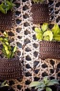 """Crocheted """"net"""" background and individual planter """"sachets"""" to create a modular vertical garden on any wall space"""