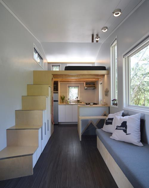 To make this tiny house interior feel as spacious as possible the owners used large windows, a full light door, and light birch plywood throughout the house.