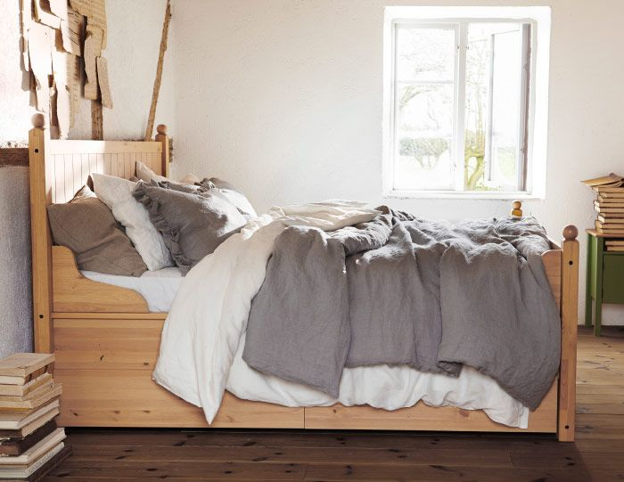 Bedroom setting with white and grey fabrics on a wooden bedframe.