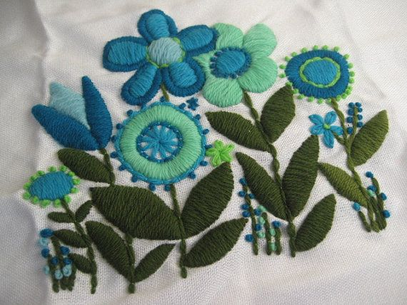 This is a super fun vintage piece! It is an embroidered type floral design in shades of blue and green yarn on a piece of white linen blend