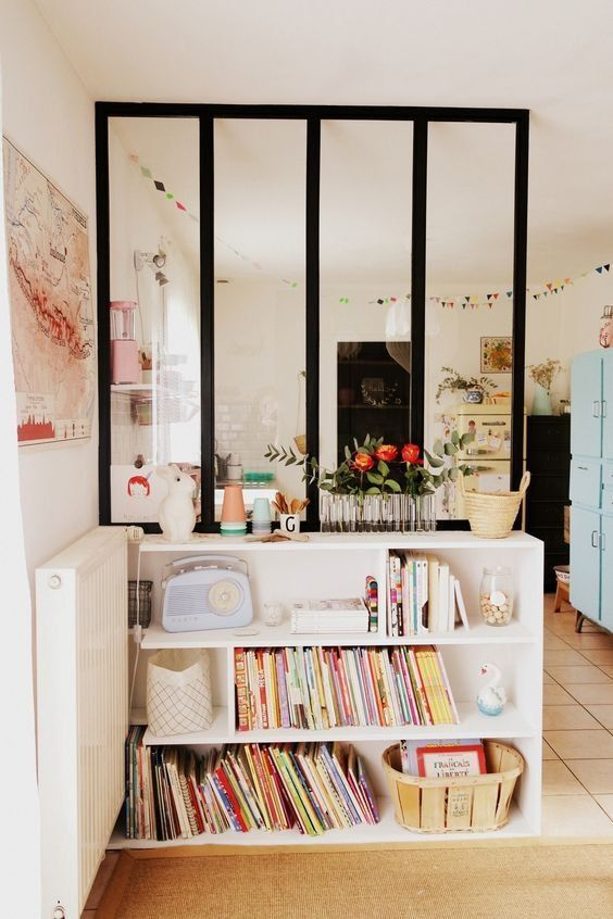 Une verrière intérieure et une petite bibliothèque pour séparer la cuisine et le salon