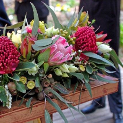 Red and Pink Ceremony Decor  Red Warratahs, blushing brides, banksias, gum nuts, and gum leaves brought a burst of colour and texture to the altar.