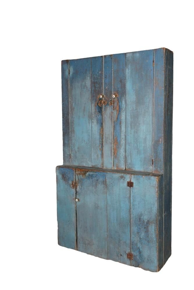 "BLUE PAINTED STEPBACK CUPBOARD - 19th c. New England, primitive pine, with robin's egg blue casein paint over gray, the interior in pale green, the upper cabinet with two doors, four shelves, the lower cabinet with a single door over two shelves, all with porcelain knob latches and original wooden thumb turns, 80"" x 45"" x 16"", 35"" to the 5"" stepback. Old dry surface and use patina."