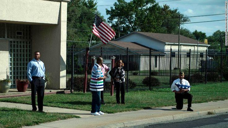 A man holding an American flag kneels as the President's motorcade passes - CNN