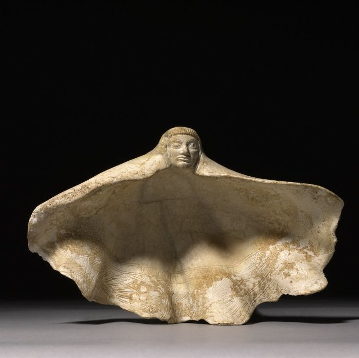700BC-650 BCE    Tridacna squamosa shell carved with a human head on the apex and two incised winged sphinxes in a register on the edge of the inner side; lotus buds and flowers in the space above the sphinxes with a band of hatched or plain triangles framed by parallel lines defining the inner edge of the field; assembled from fragments; the shell served as a container for cosmetics.    E.MED -PHOENICIAN found probably in Vulci Italy, exact production site unclear    British Museum