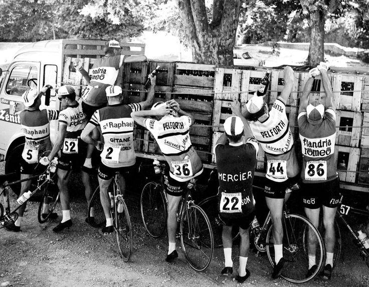 """Tour de France 1964. 11^Tappa, 2 luglio. Toulon > Montpellier. Rifornimento """"fuori programma"""" ai bordi della strada. Da sin. Pierre Everaert (1932-1989), Jean Milesi (1935), Kamiel Vyncke (1940), issato sul cassone, Rudi Altig (1937-2017), Guy Epaud (1936), Paul Vermeulen (1938), Willy Monty (1939-2014) e Guillaume Van Tongerloo (1933). Ma non è acqua..."""