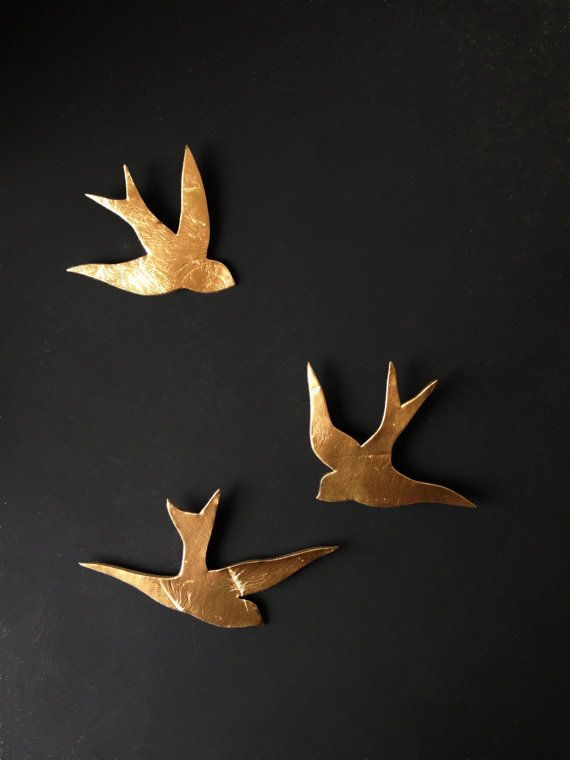 This set of three porcelain swallows have a metallic gold finish and will add rich, dramatic and whimsical style to your wall art. They are made