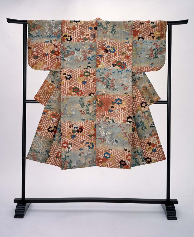 Noh theater robe (karaori) with alternating color blocks (dangawari) in light blue and orange and an overall design of autumn grasses, clematis and bamboo wickerwork in white, blue, orange, green and gold supplemental weft patterning. There is a purple plain-weave silk lining.