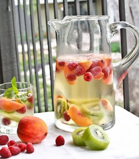 1-2 bottles of crisp white wine, I used 1 bottle Sauvignon Blanc and 1 bottle of sparkling Vino Verde  2 ripe local peaches, sliced  1 pint raspberries  2 kiwis  several sprigs of mint  0 calorie sugar- splenda or stevia