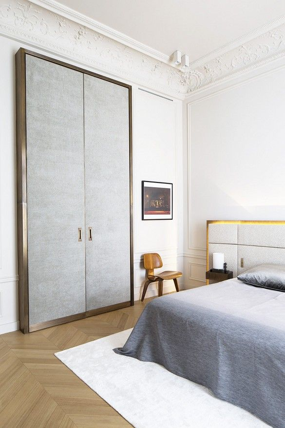 bedroom with textured sliding closets, grey bedding, wooden chair, wooden floors