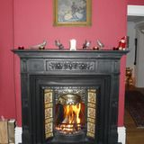 Cast iron fireplace with brass canopy and concave tiles all on a slate hearth.