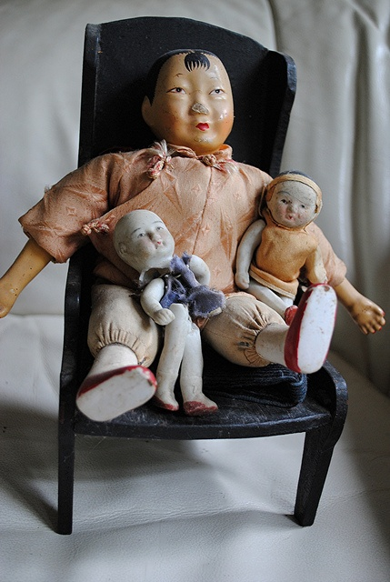 Chinese dolls sit comfortably in a black wooden chair    As a girl, my mother had a collection of tiny silk-dressed porcelain Chinese dolls. I adored them and when I was finally old enough, my mom let me hold them carefully so they wouldn't break. Years later when I was furnishing my new home, I went to a garage sale and found these adorable porcelain beauties and a black wooden chair. In my mind they belonged together and so they have remained in my Jungle home.