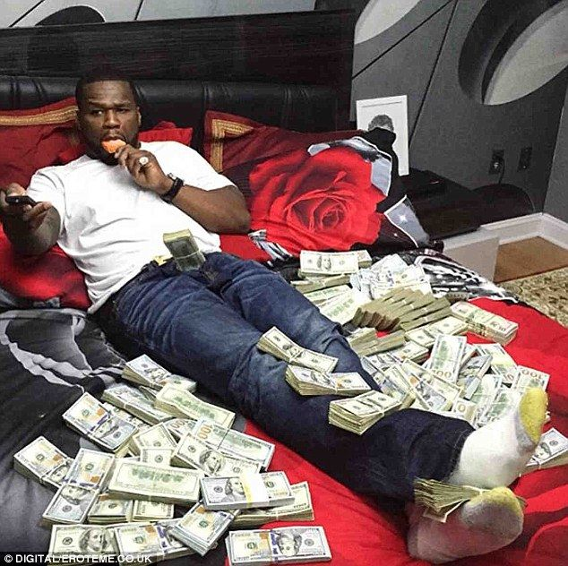 Showing off: Not content with just one flashy snap, Fifty - real name Curtis James Jackson III - shared a second photo just moments later showing him laying on his bed alongside more clusters of cash