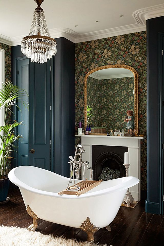 Clawfoot tub in bathroom in London Victorian home. Gorgeous dark green patterned wallpaper.