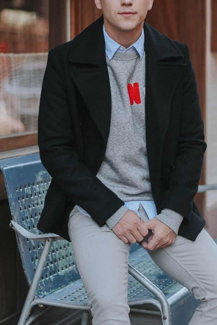 Justin from Scout Sixteen goes preppy casual with a classic twill pea coat, a statement sweater layered over an oxford shirt, and gray chinos.