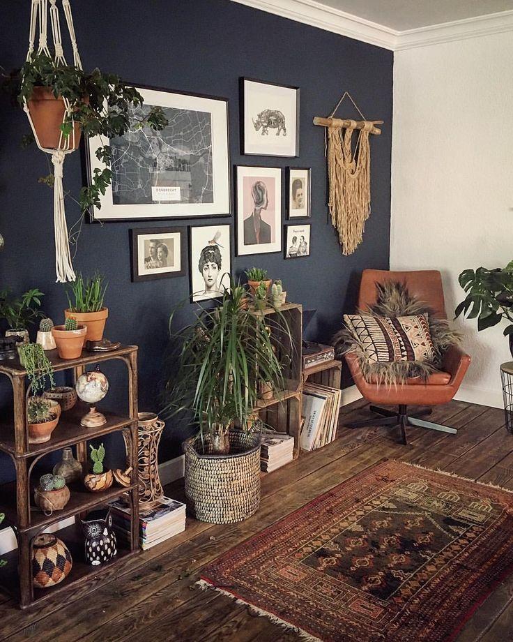 Dunkle dunkelgraue Wand mit vielen Zimmerpflanzen und erdigen Elementen – ideal für