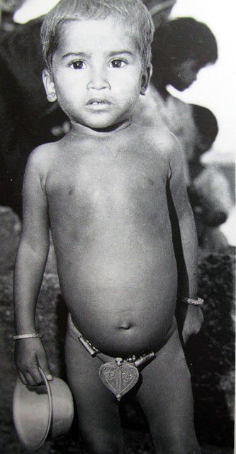 "India - Andhra Pradesh | Telegu girl wearing a silver cache-sexe plate, modesty plate, in the shape of a yoni or leaf of the sacred fit tree. | Image taken from ""Traditional Jewelry of India"" by Oppi Untracht, page 90"