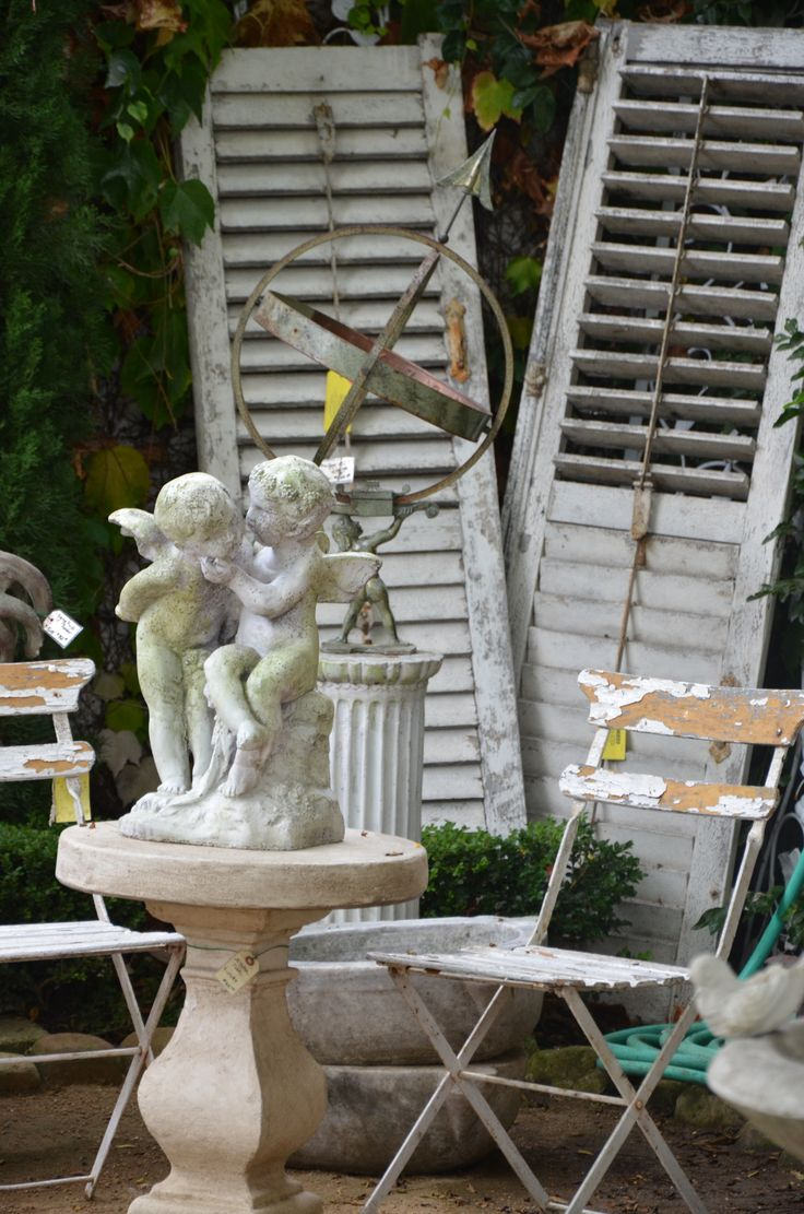 Antique French Shutters...chippy white...aged cherub statues...shabby bistro chairs.