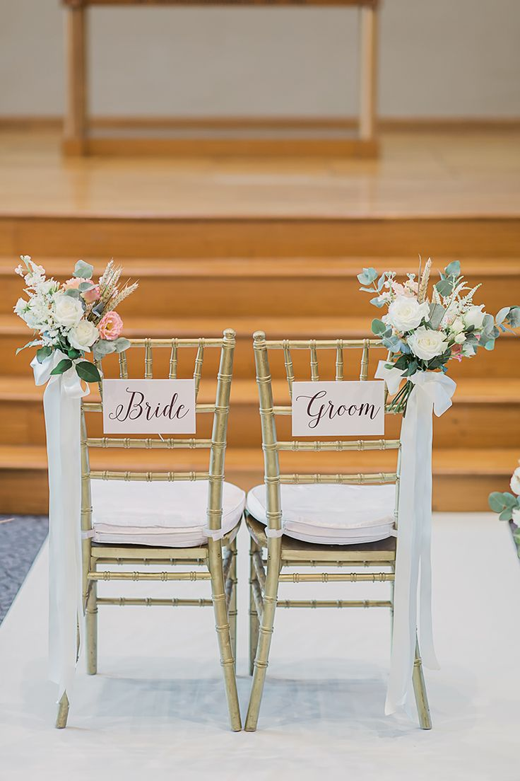 Beautiful rustic wedding chair signs and flowers.