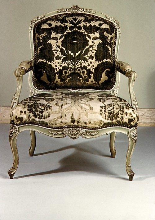 Viejo sillónLuis XV con el tapizado de terciopelo gastado