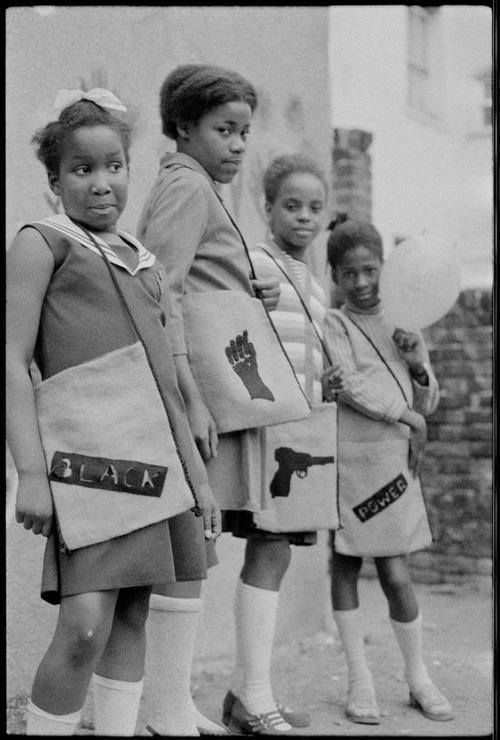 "Black Panther School Bags | 1970A group of schoolgirls carry ""radical"" school bags with signage designating the British Black Panthers, London.  Photo credit: Neil Kenlock / Autograph ABP"