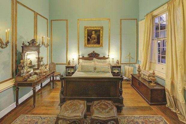 Quarto no estilo colonial tem paredes azuis e detalhes dourados