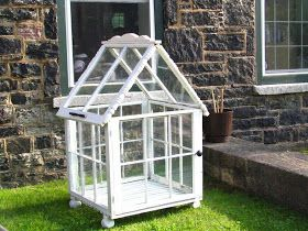 I have been collecting windows and old table legs to create my very own, one of a kind greenhouse.   Finally finished!  The front window eve...
