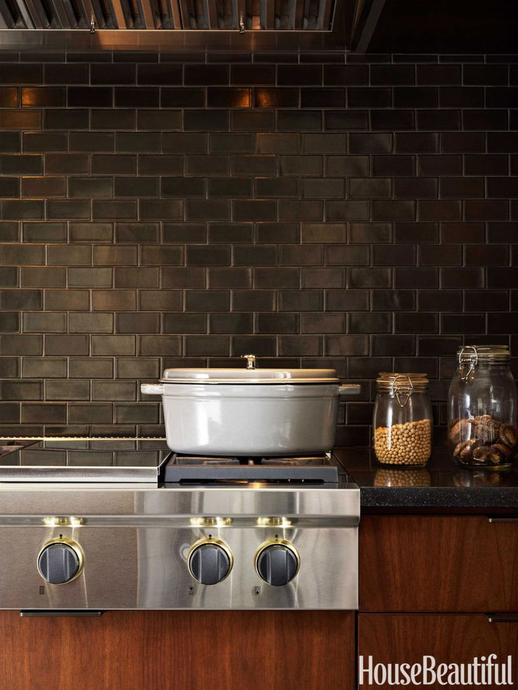 Rich woods and dark hues play up the warm side of modern style in a New York City kitchen. Designer Elena Framptonhe used New Gunmetal tile by Heath Ceramics for an iridescent backsplash.