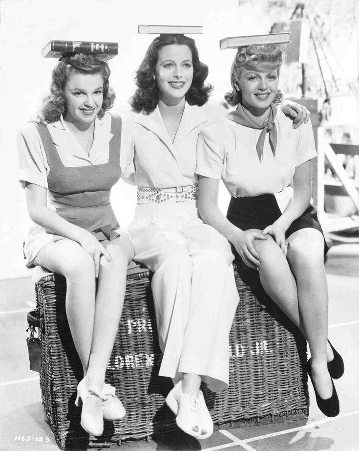 Full shot of Judy Garland as Susan Gallagher, Hedy Lamarr as Sondra Kolter and Lana Turner as Sheila 'Red' Regan all sitting on a trunk with books on their heads