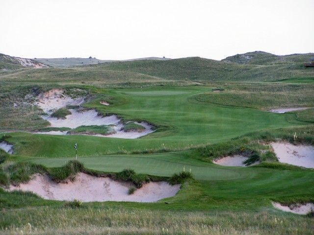 The variety of hazards at Sand Hills is astonishing, ranging from the pits around the 17th green in the foreground to the massive blow-outs up the 18th fairway in the distance...