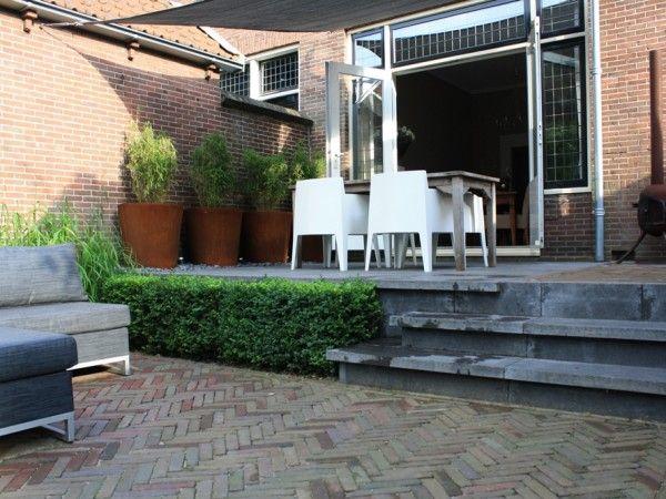 Deze jaren 30 tuin in Woerden is een kleine tuin met hoogteverschillen gelegen aan de Oude Rijn. Grote tegels, gebakken klinkers en Buxus bepalen de sfeer.