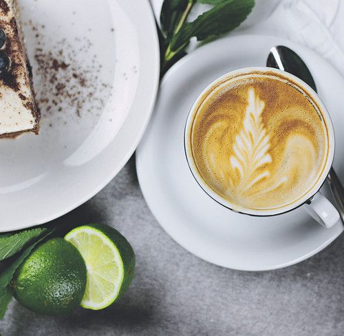 A cup of European Fancy Decaf coffee sits on a table next to a lime