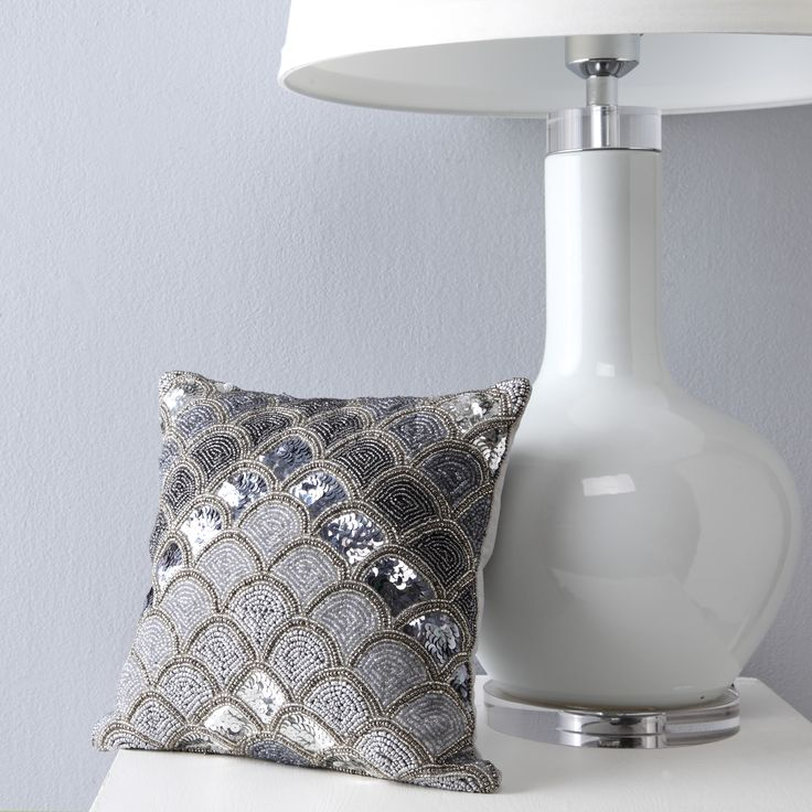 Martine Sterling injects glamour into the room. This highly decorative accessory features a lavish ensemble of silver-toned beads and sequins, in a stylised fan arrangement on the front, with plain silver reverse. Available as a 30 x 30 cm boutique cushion. #privatecollection