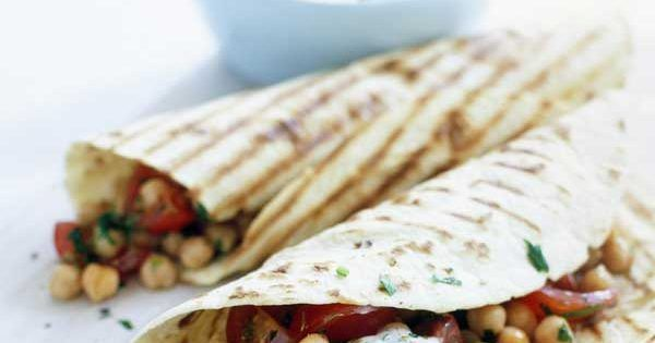 This is a great quick-to-put-together vegetarian wrap. Warm chickpeas are flavoured with cumin and chilli, cherry tomatoes are added, and the filling is wrapped in flatbreads or flour tortillas with a drizzle of yoghurt dip.