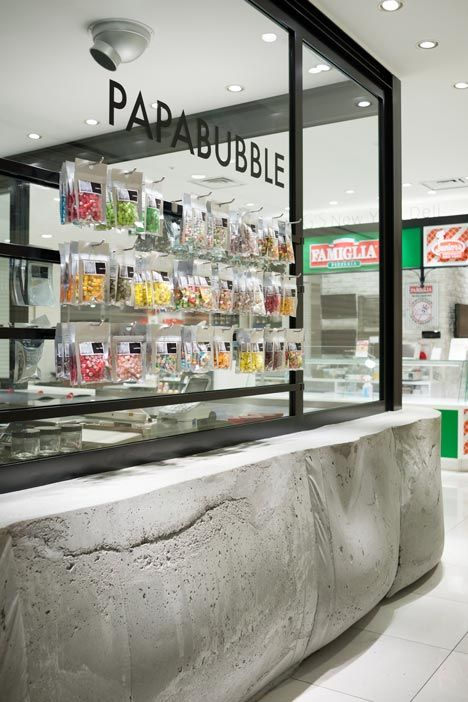Concrete bar counter cast in a strong fabric mold to express softness, plasticity and warmness of the material.