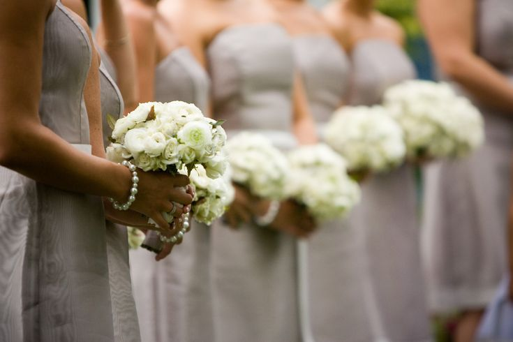Nicole's bridesmaids carried tailored round spheres of dainty white ranunculus. Joe Pulcinella Photography.