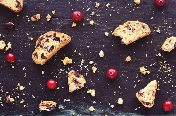Crumbled biscotti and fresh winter cranberry on dark wooden background