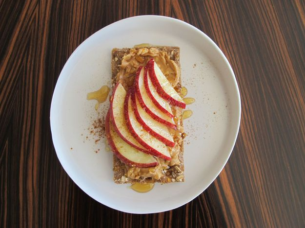 Pack a whole apple in your bag. Smear peanut, almond, cashew — whatever butter you are into — onto your crispbread. Drape a small sheet of plastic wrap over the nut butter so it doesn't smear all over, then pack it up. At snack time, thinly slice your apple, and drizzle with honey and cinnamon, which you hopefully have at work. You can substitute the apple for a banana to mix things up.