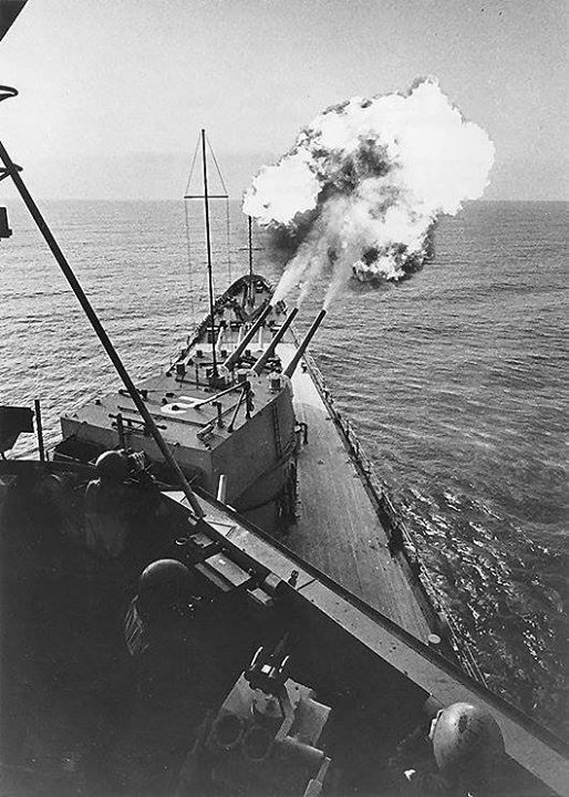 USS Canberra bombarding the coast of Vietnam March 1967. Note projectiles visible to the upper right of photograph.