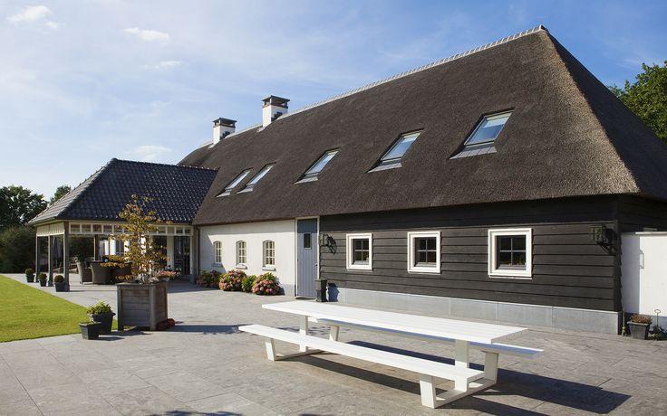 hedendaagse langgevel boerderij | Een moderne interpretatie van een sfeervol gelegen Brabantse langgevel boerderij; strak wit gestuct met rieten dak, een hardstenen plint en stallen voor de paardenhouderij. De zwarte kozijnen en luiken vormen een mooi contrast met het lichte stucwerk.
