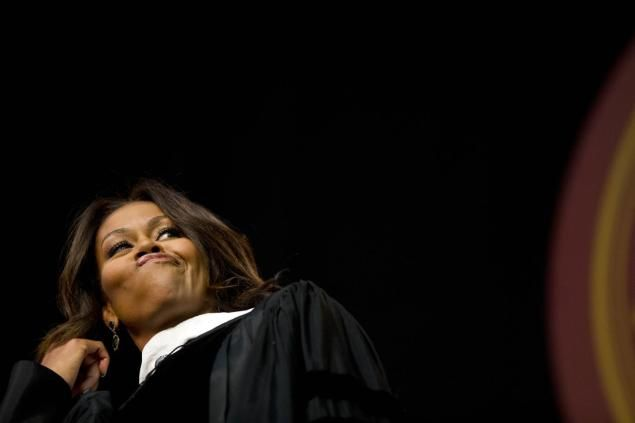 Michelle Obama flips her hair after telling the graduates that they all look amazing just before delivering the commencement address at Tuskegee University, Saturday, May 9, 2015, in Tuskegee, Ala.