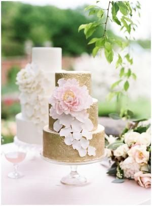 gold and white wedding cake with large fondant flower and petals by elinor