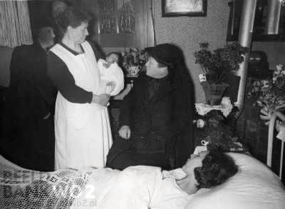 Tweede Wereldoorlog. Tilburg. Op 13 maart 1941 wordt de 100.000ste inwoner van Tilburg geboren. De baby wordt door een baker/kraamverzorgster getoond aan een mevrouw, die vermoedelijk weduwe is (zwarte kleding met sluier). Het kraambed is in de huiskamer geplaatst.