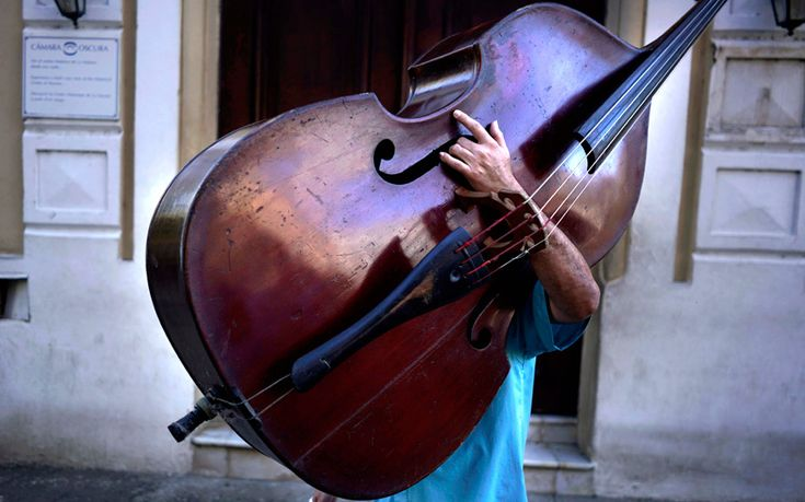 A musician carries a double bass on his walk to work in Havana, Cuba