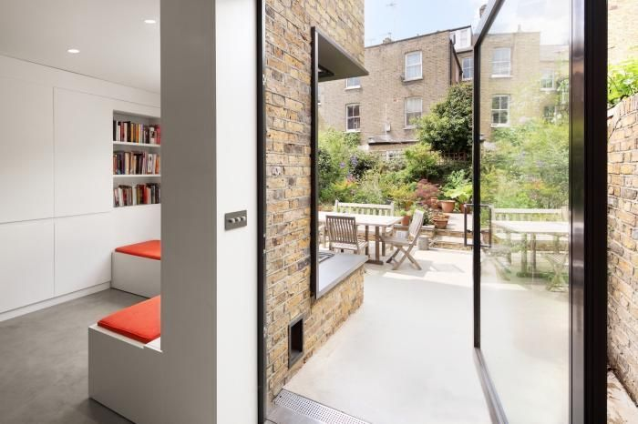 Indoor outdoor living in London townhouse remodel with white orange and brick walls